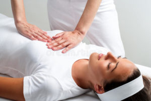 therapist-pressing-hands-womans-chest-reiki-session-close-up-chiropractor-56593814